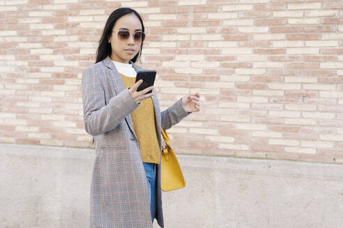 Stylish young woman wearing sunglasses using smart phone while standing against wall in city - JCZF00137