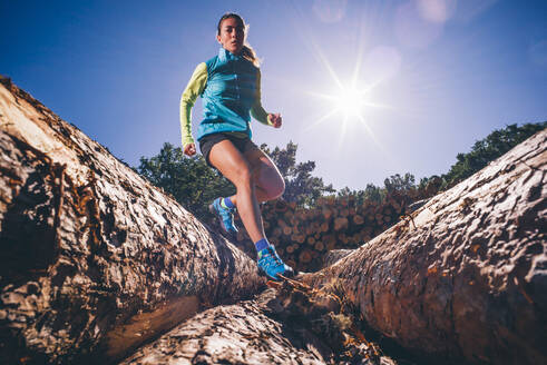 Mature woman running on logs against clear blue sky during sunny day - OCMF01338