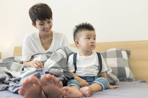 Mother with cute son relaxing on bed at home - JPTF00511
