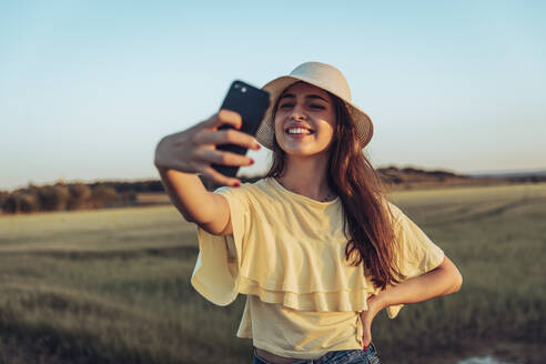 Happy young woman taking selfie through smart phone against clear sky during sunset - ACPF00749