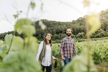 Spain, Barcelona, Penedes. Young couple of farmers strolling and enjoying their vineyards in the afternoon - JRFF04485