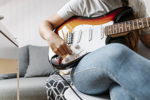 Woman adjusting knobs on electric guitar at home - JMHMF00057