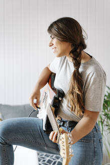 Happy woman playing electric guitar while standing at home - JMHMF00063