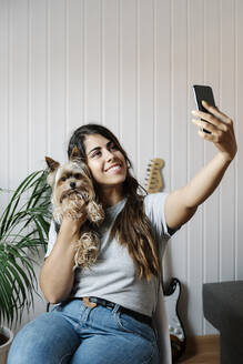 Young woman taking selfie with Yorkshire Terrier while sitting on chair at home - JMHMF00069