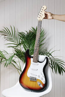Cropped image of woman's hand holding electric guitar on chair at home - JMHMF00072