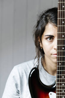 Young woman hiding behind electric guitar against wall at home - JMHMF00075
