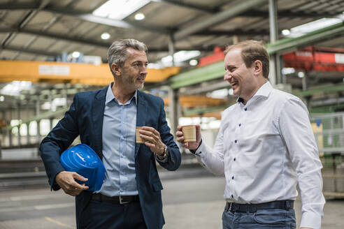 Two businessmen having a coffee break in a factory - MOEF02909