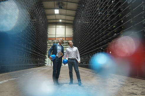 Two businessmen in a high rack warehouse of a factory - MOEF02924