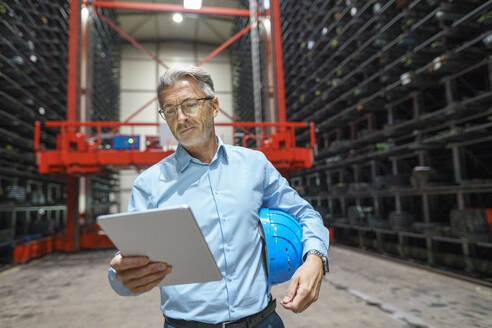 Mature businessman using tablet in a high rack warehouse of a factory - MOEF02978