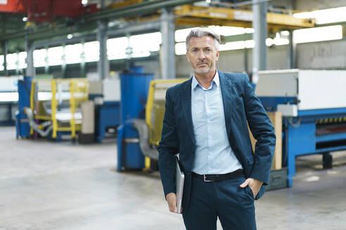 Portrait of a confident mature businessman in a factory - MOEF03020