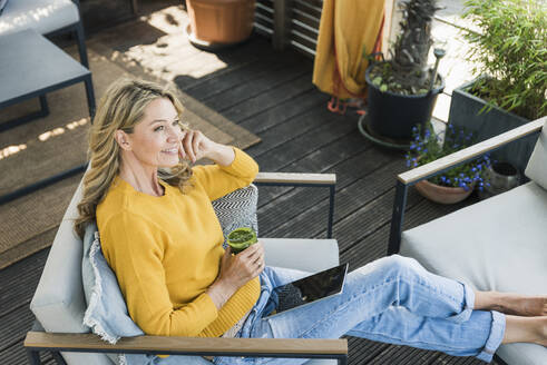 Portrait of smiling mature woman sitting on terrace with digital tablet and glass of smoothie - UUF20541