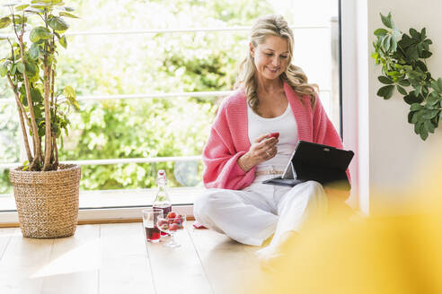 Portrait of smiling mature woman sitting on the floor at home using digital tablet - UUF20628