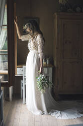 Young woman in elegant wedding dress holding bouquet looking out of the window - ALBF01259