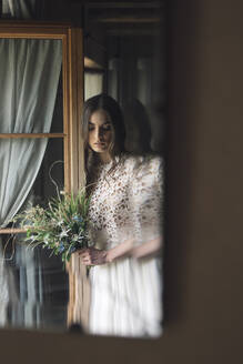 Young woman in elegant wedding dress holding bouquet looking down at window - ALBF01262