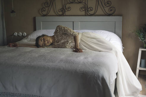 Young woman in wedding dress lying on bed - ALBF01265