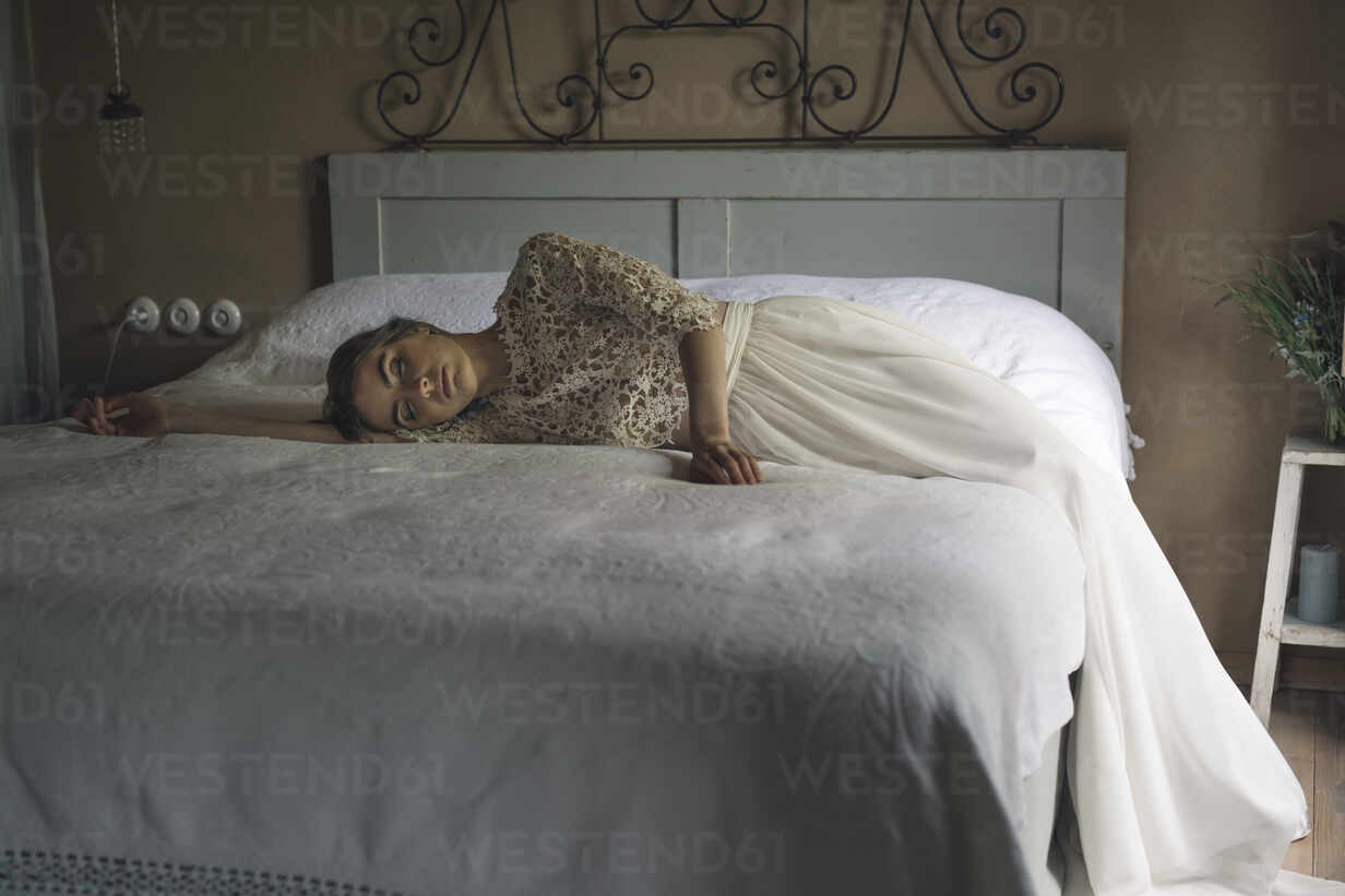 Young woman in wedding dress lying on bed - ALBF01265 - Alberto Bogo/Westend61