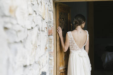 Rear view of woman in elegant wedding dress at door - ALBF01268