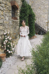 Young woman in elegant wedding dress walking at house - ALBF01277