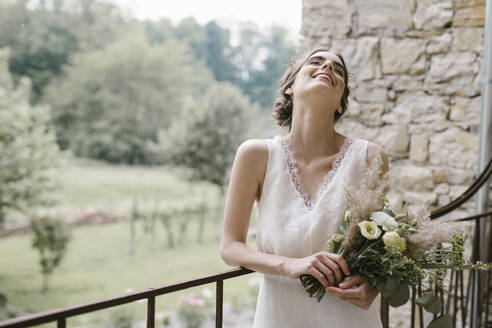 Young smiling woman in elegant wedding dress with bouquet - ALBF01280