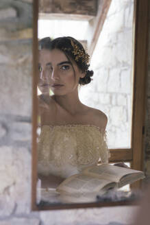 Young woman in wedding dress with book looking at mirror - ALBF01283