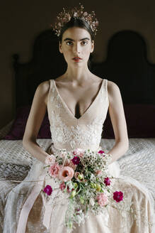 Young woman wearing wedding dress holding bouquet - ALBF01286