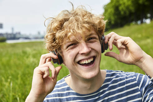 Laughing young man listening music with headphones - FMKF06211