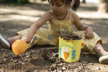 Little girl playing with soil in a park - VABF03011