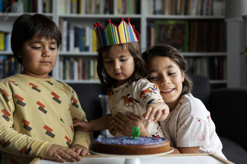 Portrait of little girl celebrating birthday with her older brothers at home - VABF03020