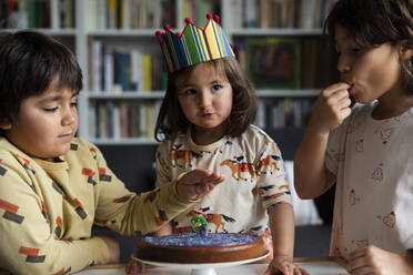 Portrait of little girl celebrating birthday with her older brothers at home - VABF03023