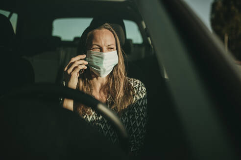 Mid adult woman with protective mask using smartphone in car - DMGF00091
