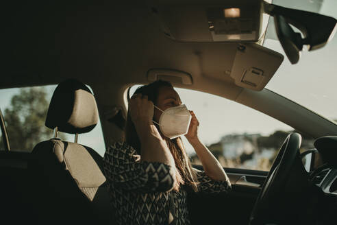 Mid adult woman with protective mask in car - DMGF00097