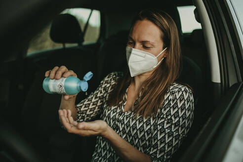 Mid adult woman with protective mask using sanitizer in car - DMGF00103