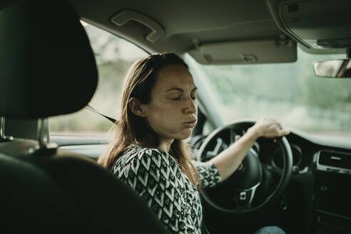 Mid adult woman breething deeply in car - DMGF00109