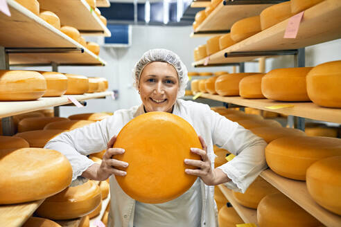 Cheese factory, smiling female worker with cheese wheel in storeroom - ZEDF03432