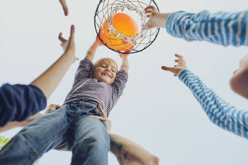 Happy boy putting basketball in hoop while playing with family against clear sky - PWF00105