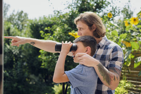 Father showing something to son looking through binoculars at yard during sunny day - PWF00126