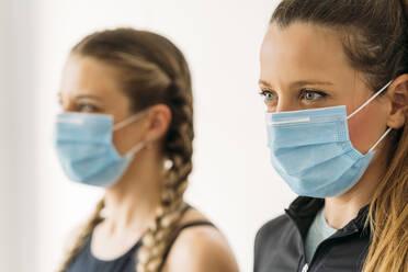 Portrait of two sporty women wearing face masks - MPPF00926