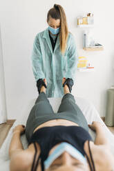 Doctor wearing face mask examining sportswoman - MPPF00938