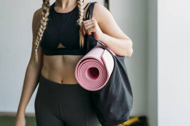 Sporty woman carrying bag with gym mat at health club - MPPF00941