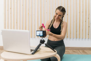 Sporty woman filming herself with camera and laptop introducing a product - MPPF00947