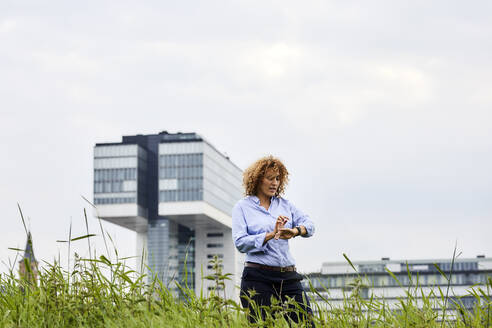 Businesswoman checking the time, crane house in the background, Cologne, Germany - MJFKF00331