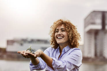 Smiling woman holding plant in her hands - MJFKF00334