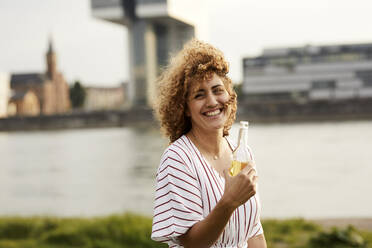 Portrait of smiling woman with glass bottle at riverside - MJFKF00343