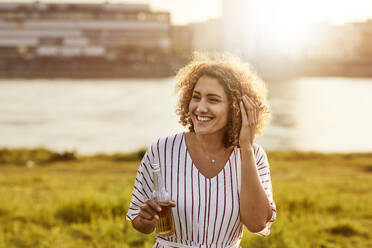 Portrait of smiling woman with glass bottle at riverside - MJFKF00346