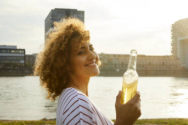 Portrait of smiling woman with glass bottle at riverside - MJFKF00352