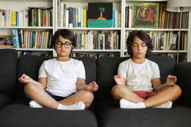 Siblings sitting on couch meditating - VABF03051