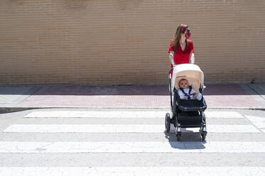 Mother wearing mask pushing son in baby carriage while walking on street - JCMF00796