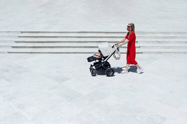 Mother wearing mask pushing son in baby carriage while walking on town square - JCMF00799
