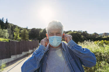Senior man with protective mask outdoors - AFVF06595