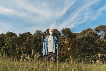 Senior man with protective mask standing on meadow - AFVF06598
